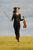 Girl with violin runs on grass against sky Royalty Free Stock Image