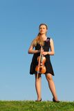 Girl with violin stands on grass against  sky Stock Image