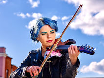 Girl violinist playing  aganist sky with clouds Stock Image