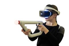 Girl in virtual glasses shoots virtual toy weapon isolated on white background. Girl in virtual glasses shoots virtual weapons isolated on white background stock photo