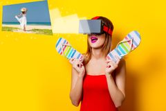 Girl with virtual reality glasses dreaming about vacation. Young redhead girl with virtual reality glasses dreaming about vacation on yellow background Stock Photos
