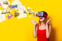 Girl with virtual reality glasses dreaming about vacation. Young redhead girl with virtual reality glasses dreaming about vacation on yellow background Stock Image