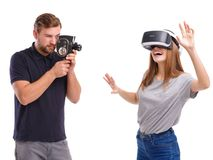 A girl in virtual reality glasses and next to a guy taking pictures of on a retro camera. Isolated. royalty free stock image