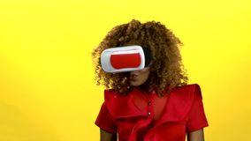 Girl in virtual reality glasses is watching an interesting video. Yellow background. Slow motion. African american girl in virtual reality glasses is watching an stock video footage