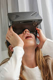 Girl in Virtual Reality headset looking up and trying to touch o Royalty Free Stock Photo