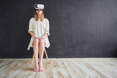 The girl in the virtual reality helmet. The girl in white sitting on a chair in the virtual reality helmet royalty free stock image