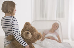 Girl visiting seriously ill mother. Little girl visiting her seriously ill mother lying in hospital bed Stock Photos