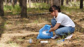 Girl volunteer collects garbage in a biodegradable bag, taking care of the environment. The concept of environmental