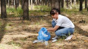 Girl volunteer collects garbage in the woods, putting it in a garbage bag. The concept of environmental protection and