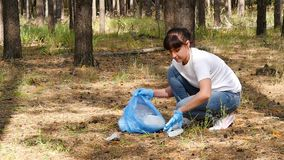 Girl volunteer takes care of the environment, collecting garbage in the woods. The concept of caring for the environment