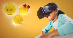 Girl in VR with emojis and flares against yellow background. Digital composite of Girl in VR with emojis and flares against yellow background Royalty Free Stock Image