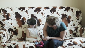 Girl in VR goggles on sofa with mother stock footage