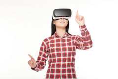 Girl in VR headset making choose and pointing by fingers. Stock Photo