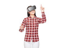 Girl in VR headset making choose and pointing by fingers. Brunette girl making choose and playing game in cyberspace, pointing by fingers. Woman in headset of Royalty Free Stock Photo