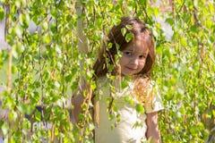 The girl vygladyvat because of birch tree branches. Portrait of the Girl, vygladyvayushchy because of birch tree branches Stock Photography