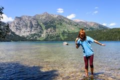 Girl wading in clear mountain lake stock image
