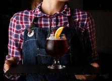 Girl waiter holds an alcoholic cocktail.  royalty free stock photography
