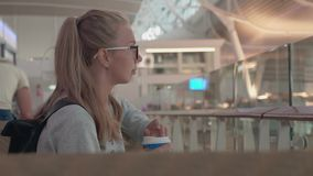 Girl Waiting in an Airport. Young blonde girl wearing glasses and holding passport, and ticket waiting for the flight at the airport. Woman drinking coffee stock video