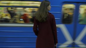 Girl waiting for arriving train at the subway station. Rear view of girl waiting at train station. Train arrives. 4K stock video footage