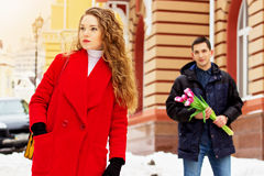 Girl is waiting for her boyfriend, who is standing with flowers behind her. Young couple walking together in the city. Royalty Free Stock Photo
