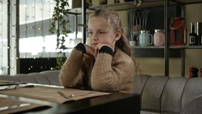Girl is waiting for her dinner. Small girl is waiting for her dinner in restaurant stock video footage