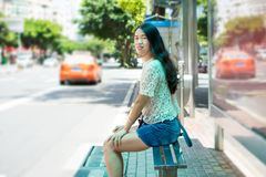 Girl waiting for transportation at bus stop Stock Image