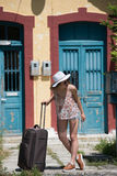 Girl waiting with rolling upright suitcase at docks Stock Image