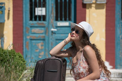 Girl waiting with rolling upright suitcase at docks Stock Photo