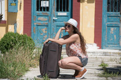 Girl waiting with rolling upright suitcase at docks. Pretty girl with curly hair wear casual clothes, sunglasses and panama hat, waiting with rolling upright Royalty Free Stock Photo