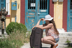 Girl waiting with rolling upright suitcase at docks Royalty Free Stock Image