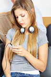 Girl in waiting room with smartphone Royalty Free Stock Photos