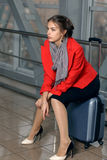 Girl waiting sitting on a suitcase Stock Image