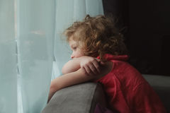 Girl waiting for someone and looking out the window Royalty Free Stock Image