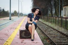Girl waiting for train. On empty railroad platform Stock Photos
