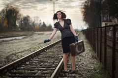 Girl waiting for train. On empty railroad platform Stock Photo