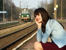 Girl waiting for the train. Young girl waiting for the train on the empty railway platform with an old suitcase Stock Photo