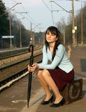 Girl waiting for the train. Young girl waiting for the train on the empty railway platform with an old suitcase Stock Photography