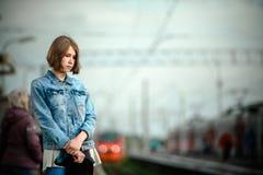 Girl waiting train on the platform of railway station stock image