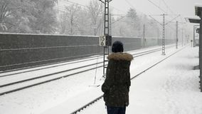 Girl waiting the train in winter time. Snow and frost stock footage