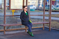 Girl waiting for transport at the bus stop Stock Photos