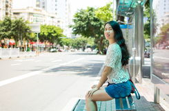 Girl waiting for transportation at bus stop Stock Images