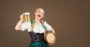 Girl waitress oktoberfest in national costume with a mug of beer Stock Photos