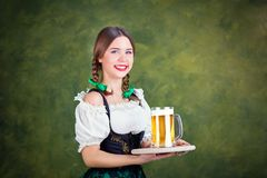 Girl waitress oktoberfest in national costume with a mug of beer Royalty Free Stock Photo