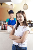 Girl And Waitress Standing Arms Crossed At Ice Cream Parlor. Portrait of confident girl and waitress standing arms crossed at ice cream parlor Royalty Free Stock Photos
