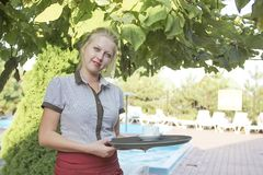 Girl waitress with a tray of summer. Server royalty free stock photo