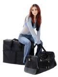 Girl waits sitting on bag Stock Image
