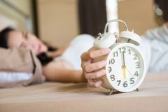 Girl wake up to turn off alarm clock Royalty Free Stock Photos