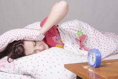 Girl wakes up the clock in morning Stock Photo