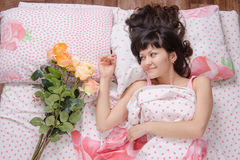Girl wakes up and enjoys bouquet of flowers donated by Royalty Free Stock Images