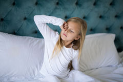Girl waking up on bed in bedroom Stock Photos